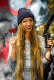 Belle fille à la mode dans des vêtements élégants avec sucrerie et tasse de fond de graffiti une grandes dans des ses mains Photos stock