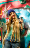 Belle fille à la mode dans des vêtements élégants avec sucrerie et tasse de fond de graffiti une grandes dans des ses mains Photographie stock libre de droits