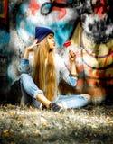 Belle fille à la mode dans des vêtements élégants avec sucrerie et tasse de fond de graffiti une grandes dans des ses mains Image stock