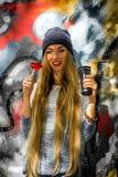 Belle fille à la mode dans des vêtements élégants avec sucrerie et tasse de fond de graffiti une grandes dans des ses mains Images libres de droits