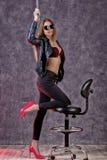 Belle fille à la mode urbaine dans la veste en cuir noire et des jeans posant sur une chaise d'arbitre images stock