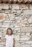 Belle fille à la plage devant une maison en pierre Image stock