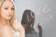 Belle fille écrite sur un miroir dans le rouge à lèvres, I Photo stock