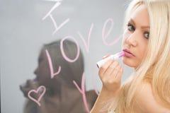 Belle fille écrite sur un miroir dans le rouge à lèvres, I Image stock