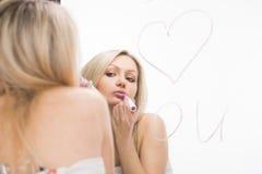 Belle fille écrite sur un miroir dans le rouge à lèvres, I Photographie stock