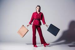 belle fille élégante dans des vêtements à la mode rouges avec des paniers, photos stock