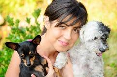 Belle fille étreignant deux petits chiens Photos stock