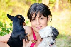 Belle fille étreignant deux petits chiens Image libre de droits