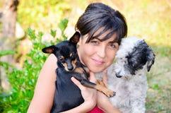 Belle fille étreignant deux petits chiens Image stock