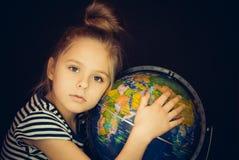 Belle fille étreignant un globe Image libre de droits