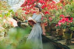 Belle fille adulte en serre chaude d'azalée lisant un livre et rêvant dans une belle rétro robe photo stock