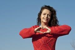 Belle fille affichant le signe de coeur photographie stock libre de droits
