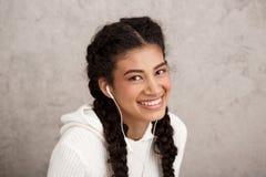 Belle fille africaine dans des écouteurs souriant au-dessus du fond beige Image stock