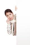 Belle fille asiatique avec l'écharpe choquée, jetant un coup d'oeil par derrière le bla Image libre de droits