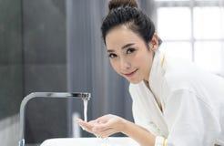 Belle fille asiatique dans le peignoir se lavant le visage avec de l'eau au-dessus d'?vier de salle de bains et regardant la cam? image stock