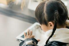 Belle fille asiatique employant le comprimé, la première éducation et l'étude Images libres de droits