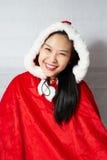 Belle fille asiatique heureuse dans des vêtements de Santa Claus Images libres de droits