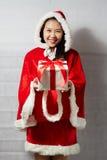 Belle fille asiatique heureuse dans des vêtements de Santa Claus Photographie stock libre de droits