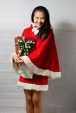 Belle fille asiatique heureuse dans des vêtements de Santa Claus Photo libre de droits