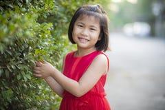 Belle fille asiatique portant la robe rouge de jupe se déplaçant avec le visage de bonheur extérieur photos stock