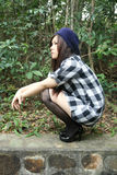 Belle fille asiatique s'accroupissant Image stock