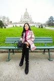 Belle fille asiatique s'asseyant sur un banc près du Sacre-Coeur dedans Image stock