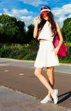 Belle fille asiatique sexy posant sur des patins de rouleau de vintage dans l'équipement, les espadrilles et le chapeau rouge à l Photographie stock libre de droits