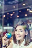 Belle fille asiatique tenant un globe dans sa main dans le sho de cofffee Photographie stock