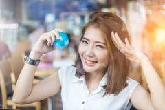 Belle fille asiatique tenant un globe dans sa main dans le sho de cofffee Photo stock
