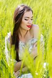 Belle fille au champ vert Photographie stock