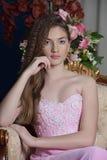 Belle fille aux cheveux foncés dans la robe de soirée rose se reposant dans une chaise images libres de droits
