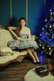 Belle fille aux cheveux foncés s'asseyant sur le sofa i image libre de droits
