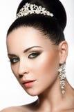 Belle fille aux cheveux foncés dans l'image d'une jeune mariée avec un diadème dans ses cheveux Visage de beauté Images stock