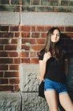 Belle fille aux cheveux longs sur un fond de mur de briques Le concept d'une femme seule images stock