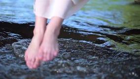 Belle fille aux pieds nus plongeant ses pieds dans le courant débordant frais de rivière banque de vidéos