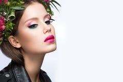 Belle fille avec beaucoup de fleurs dans leurs cheveux et maquillage rose lumineux Image de ressort Visage de beauté Photos libres de droits