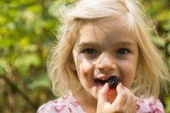 Belle fille avec Blackberry dans le jardin Photographie stock libre de droits