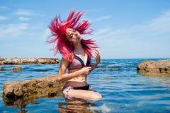 Belle fille avec couler les poils rouges sur le Bea Photo stock