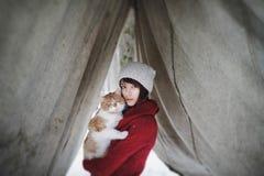 Belle fille avec dans le chandail rouge et le chapeau se tenant et jouant avec le petit chat pelucheux en parc neigeux d'hiver An Image libre de droits