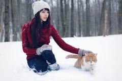 Belle fille avec dans le chandail rouge et le chapeau se tenant et jouant avec le petit chat pelucheux en parc neigeux d'hiver An Photos stock