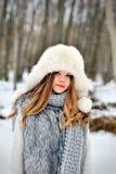 Belle fille avec de longs cheveux bouclés dans le chapeau tricoté d'écharpe et de fourrure ayant l'amusement extérieur dans la fo photographie stock