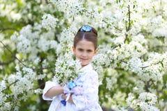 Belle fille avec de longs cheveux dans un jardin de floraison Photo stock