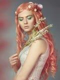 Belle fille avec de longs cheveux et fleurs roses Images stock
