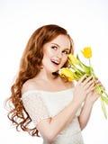 Belle fille avec de longs cheveux magnifiques rouges tenant les tulipes jaunes photo stock