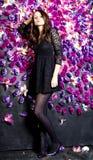 Belle fille près du mur avec les fleurs violettes Photo stock