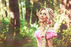 Belle fille avec de longs cheveux tressés dans une tresse, dans le corset et la robe rose magnifique Photos stock