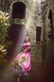 Belle fille avec de longs cheveux tressés dans une tresse, dans le corset et la robe rose magnifique Images libres de droits