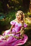 Belle fille avec de longs cheveux tressés dans une tresse, dans le corset et la robe rose magnifique Photographie stock libre de droits