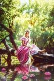 Belle fille avec de longs cheveux tressés dans une tresse, dans le corset et la robe rose magnifique aux nénuphars de lac Photos libres de droits