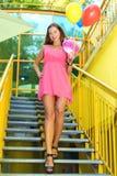Belle fille avec de longues jambes dans la robe rose avec photographie stock libre de droits
